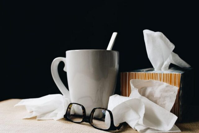 a shot of used tissues and barley tea in a mug depicting a person has a cold